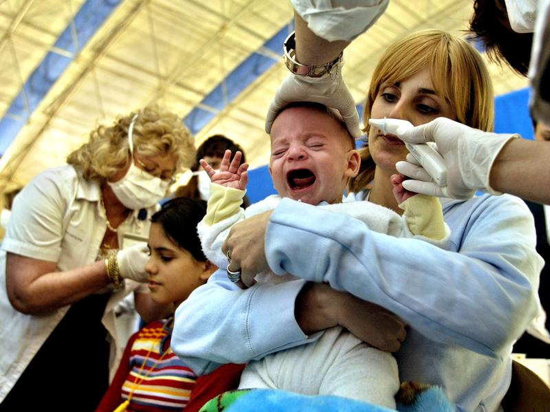 On the lookout for SARS, an employee checks a baby's temperature at the Ben Gurion Airport in Israel, in 2003. The deadly virus quickly spread around the world once it reached Hong Kong, a central travel hub.
