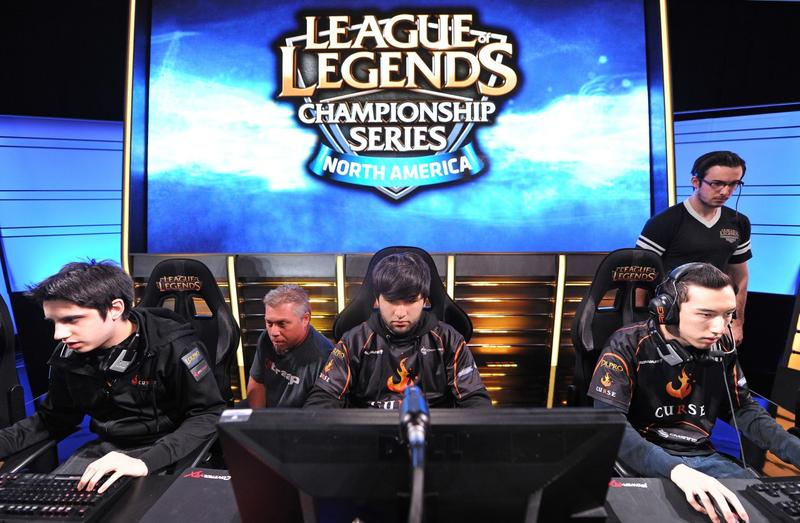 Team Curse players Christian 'IWillDominate' Rivera (left), Joedat 'Voyboy' Esfahani (center) and David 'Cop' Roberson (right) prepare for the start of a match as two broadcast technicians (background) prepare the live video feed, during the League of Legends North American Championship Series Spring round robin competition, at the MBS Media Campus in Manhattan Beach, Calif., February 22, 2014. (Robyn Beck/AFP/Getty Images)