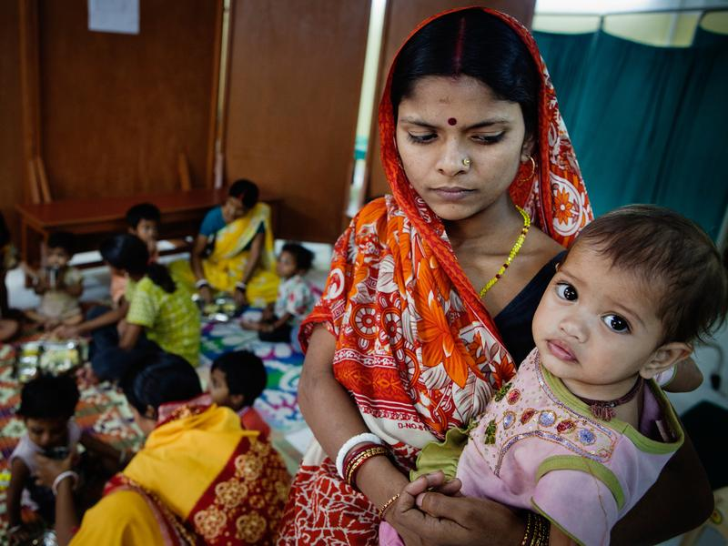 A mother holds her child at a diarrhea treatment center set up and run by the public health organization Calcutta Kids.