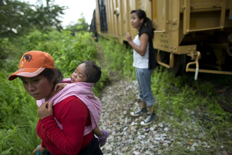"Guatemalan migrant Gladys Chinoy, 14, right, waits with more than 500 other migrants, many traveling with small children, beside the stuck freight train on which they were traveling, outside Reforma de Pineda, Chiapas state, Mexico, June 20, 2014. Reached by phone in New York City, Gladys' mother said she was aware of the dangers but had finally decided they were worth it after five years apart. The mother said, ""if she gets across, she can stay here, that's what you hear.""(Rebecca Blackwell/AP)"