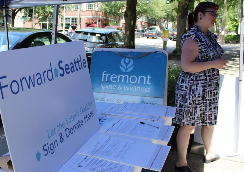 Forward Seattle co-chair Kathrina Tugadi collecting signatures at the recent Fremont Fair. (Deborah Wang/KUOW)