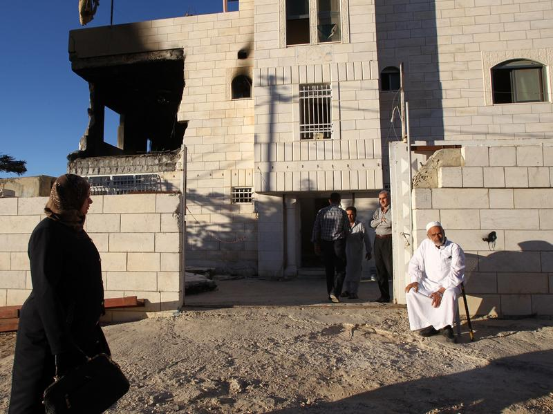 Relatives gather outside the damaged house of Amer Abu Eishe, a Palestinian member of Hamas in Hebron whom Israel named as one of two prime suspects in the murder of three kidnapped Israeli teenagers. The house was damaged in a raid.