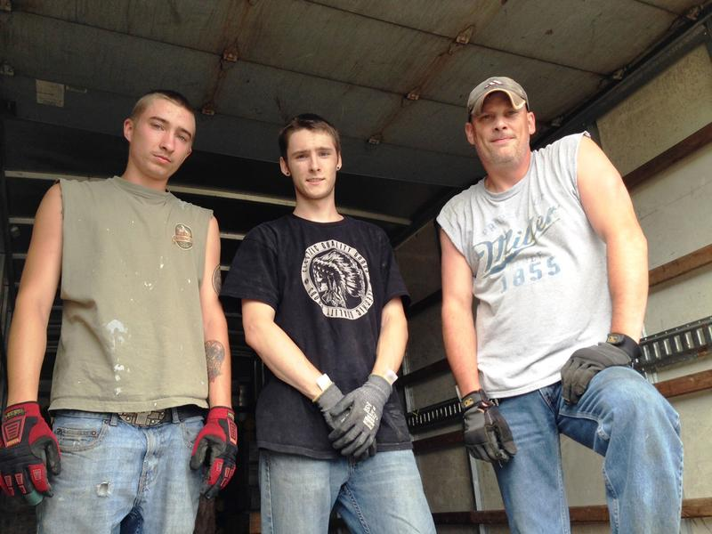 Brandon Weaver, right, and his fellow crew members pose in the back of a Budget rental truck. They say being back at work is helping them cope with the death of their co-worker. (Northwest News Network)