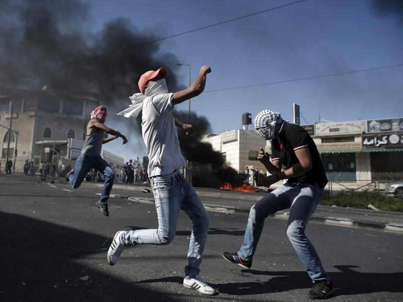 Palestinian protesters throw stones toward Israeli police during clashes in the Shuafat neighborhood in Israeli-annexed Arab East Jerusalem on Wednesday, after a Palestinian teenager was apparently abducted in what's thought to be an act of revenge for the murder by militants of three Israeli youths.