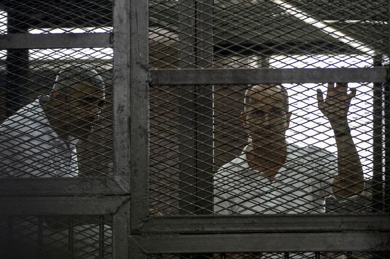Al-Jazeera news channel's Australian journalist Peter Greste (right) and Egyptian-Canadian Mohamed Fadel Fahmy listen to the verdict inside the defendants cage during their trial for allegedly supporting the Muslim Brotherhood, June 23, 2014, in Egypt. (Khaled Desouki/AFP/Getty Images)
