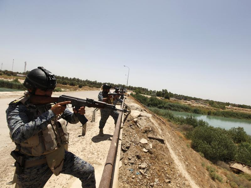 Iraqi policemen take up positions on a bridge north of Baghdad on Monday. There's a consensus among Western and Middle Eastern states that militants from the Islamic State pose a serious threat to the region. But there's no sign yet that countries like the United States, Russia and Iran are prepared to work together.