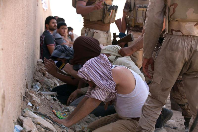 Members of Iraqi security detain supporters of Shiite Sheikh Mahmud al-Hassani al-Sarkhi, following clashes in the shrine city of Karbala on July 2, 2014. (Mohammed Sawaf/AFP/Getty Images)
