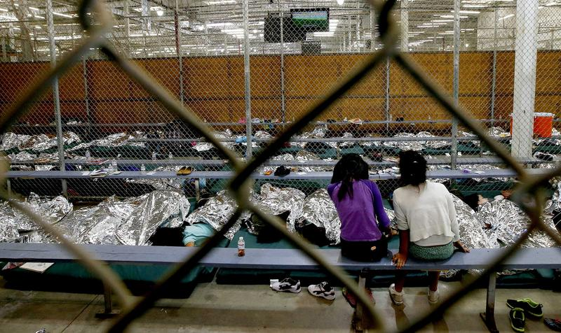 Two young girls watch the World Cup in their holding area at the U.S. Customs and Border Protection Nogales Placement Center on June 18. Hundreds of mostly Central American immigrant children are being processed and held in Nogales, Arizona. (Ross D. Franklin-Pool/Getty Images)