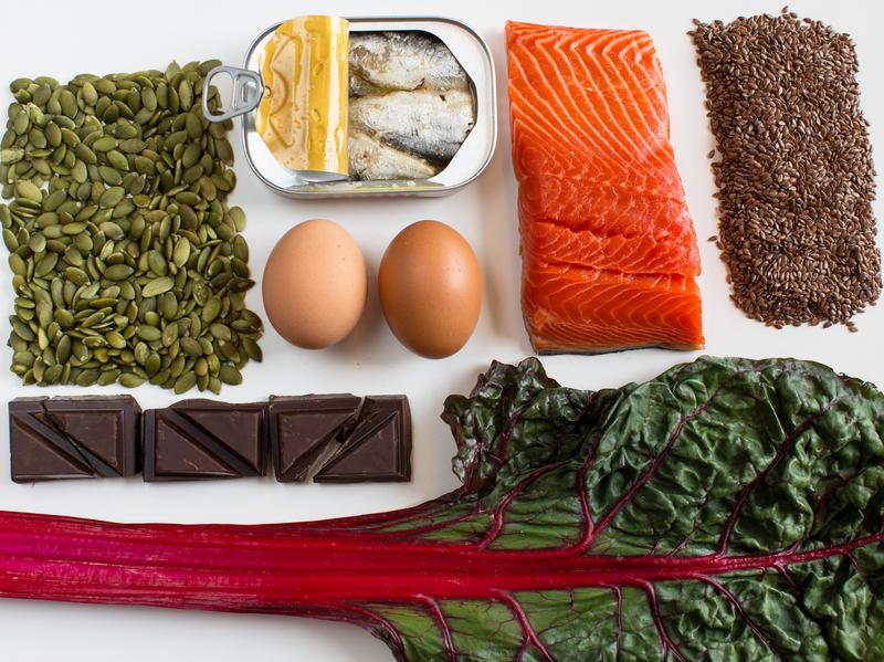 A nutrient-dense diet may help tamp down stress. And these foods may help boost our moods (clockwise from left): pumpkin seeds, sardines, eggs, salmon, flax seeds, Swiss chard and dark chocolate.