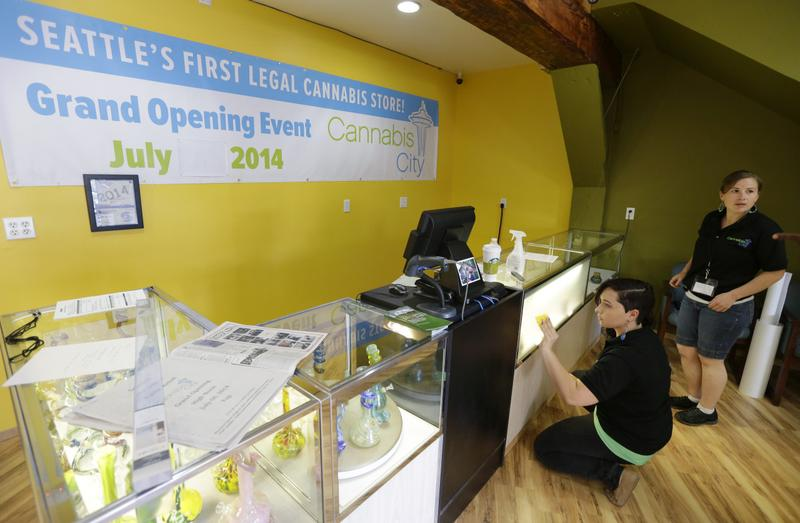 Amber McGowan, left, and Krystal Klacsan, right, work Monday, July 7, 2014, at the recreational marijuana store Cannabis City in Seattle to apply a state-mandated frosted film to the front of a display case that will contain pot varieties when legal sales begin on Tuesday, July 8, 2014. The store will be the first and only store in Seattle to initially sell recreational marijuana on Tuesday. (Ted S. Warren/AP)