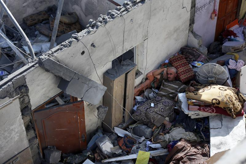 A Palestinian man lies amid the rubble of his house following an Israeli air strike that killed eight people, including members of his family, on July 10 in the southern Gaza Strip city of Khan Yunis. The Israeli air force overnight hit more than 300 Hamas targets in the Gaza Strip in response to rocket fire from the besieged Palestinian territory, an army spokesman said. (Thomas Coex/AFP/Getty Images)