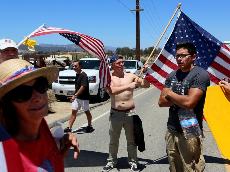 Miguel Hernandez (right), an immigrant rights activist, stands among anti-immigration activists outside of the U.S. Border Patrol's Murrieta station on Monday. The federal agency says it will not fly more detained migrants to be processed at the facility.