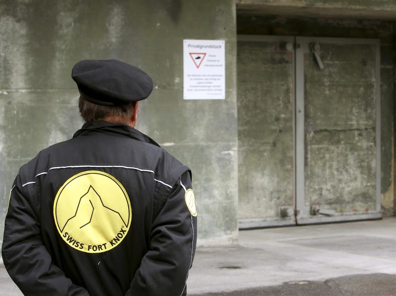 A security guard stands in front of a gate of the Swiss Fort Knox bunker in the mountains near the Swiss Alpine resort of Saanen.