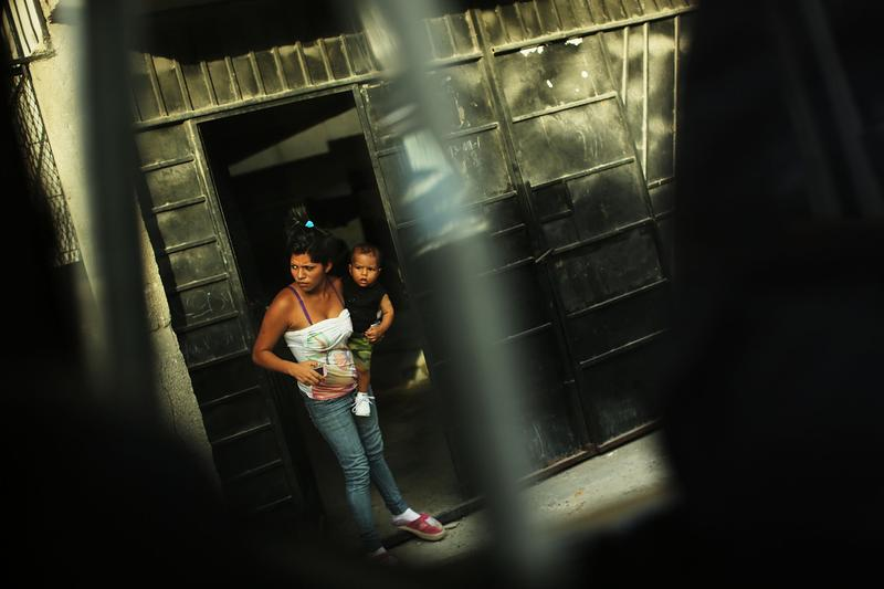 A woman and her son look out of a doorway in a neighborhood with heavy gang violence on July 20, 2012 in Tegucigalpa, Honduras. Honduras now has the highest per capita murder rate in the world and its capital city, Tegucigalpa, is plagued by violence, poverty, homelessness and sexual assaults. (Spencer Platt/Getty Images)