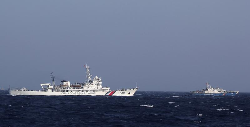 In this photo from May 15, 2014, China Coast Guard 3411 vessel, left, and Vietnam Coast Guard 4032 vessel sail in the waters claimed by both countries in the South China Sea. China's deployment of an oil rig off Vietnam's coast prompted a tense sea standoff and touched off deadly anti-China rioting. China recently removed the oil rig, though they have vowed to return. (Hau Dinh/AP)