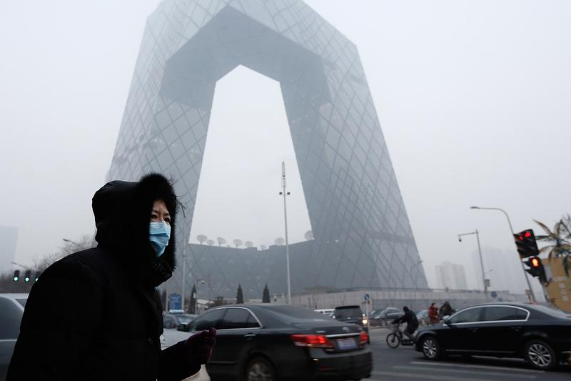 A woman wearing a mask walks past the CCTV Building during severe pollution in January 2013 in Beijing. That week, the AQI in Beijing hit 755, even though it normally maxes out at 500. (Lintao Zhang/Getty Images)