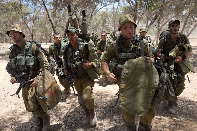 Israeli soldiers of an Infantry unit walk to their deployment area near Israel's border with the Gaza Strip on July 18. (Menahem Kahana/AFP/Getty Images)