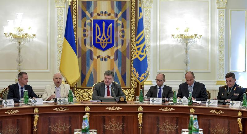 Ukrainian President Petro Poroshenko, third left, chairs a Security Council meeting in Kiev, Ukraine yesterday. Poroshenko called the downing of a Malaysia Airlines passenger plane an act of terrorism and called for an international investigation into the crash, insisting that his forces did not shoot down the plane. From right, Ukrainian Defense MInister Valery Heletey, Head of the Security Council Andriy Parubiy, Prime Minister Arseniy Yatsenyuk, Petro Poroshenko, parliament speaker Oleksandr Turchynov. (Mykola Lazarenko/AP Photo/Presidential Press Service)