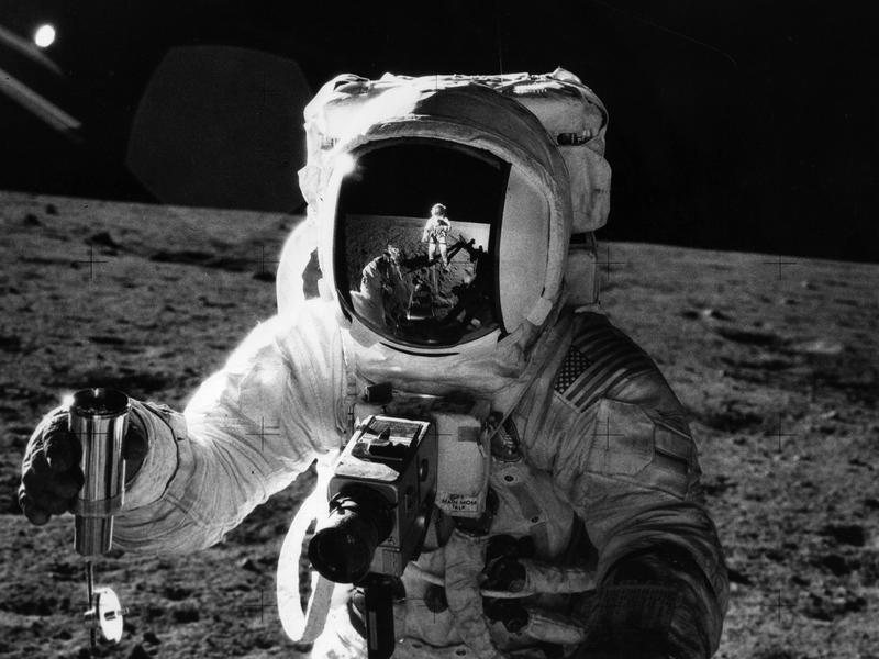 "During the Apollo 12 mission, astronaut Alan Bean holds a container of lunar soil. The astronaut Charles ""Pete"" Conrad, who took the photograph, is reflected in Bean's faceshield. Bean says he used to think that in his lifetime, we'd build a base on the moon and start preparing to travel to Mars."