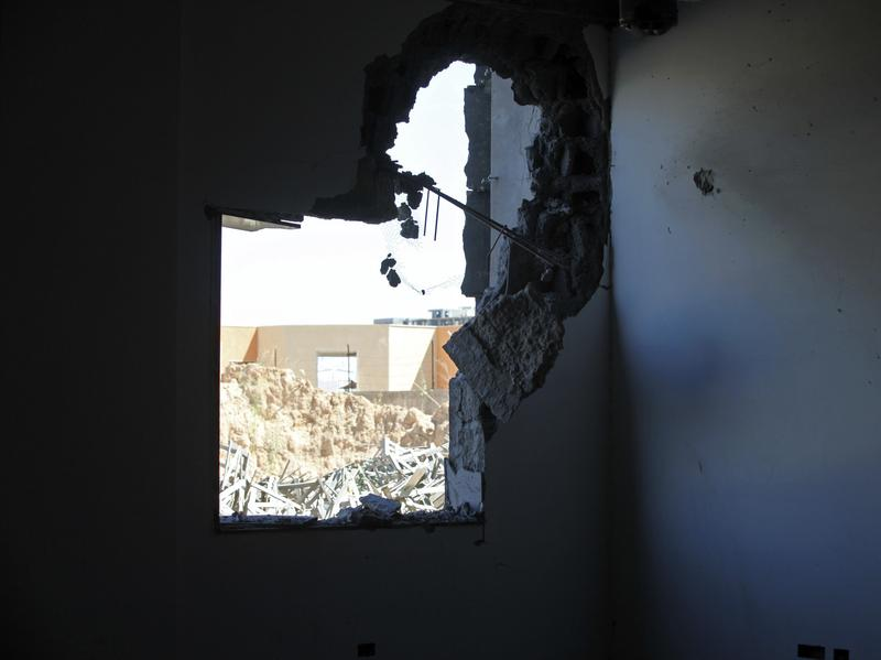 A damaged building and debris outside are seen Sunday after heavy fighting broke out between rival militias near the airport in the Libyan capital, Tripoli.