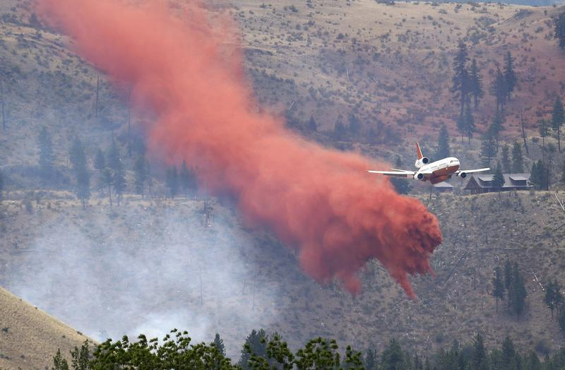 A DC-10 air tanker pulls up after dropping fire retardant over a wildfire Saturday, July 19, 2014, near Carlton, Wash. (Elaine Thompson/AP)