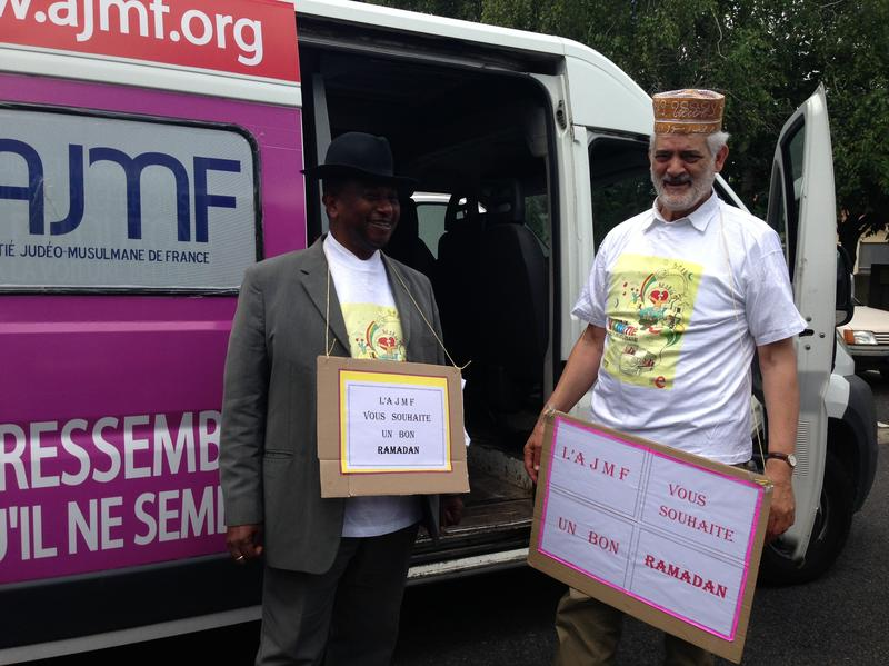 Rabbi Michel Serfaty (right), head of the Jewish-Muslim Alliance of France, stands next to a Muslim cleric, or imam, as they both hold signs wishing Muslims a happy Ramadan. The rabbi and the imam have also traded hats. Despite efforts by Serfaty's group, a record number of French Jews are expected to move to Israel this year.
