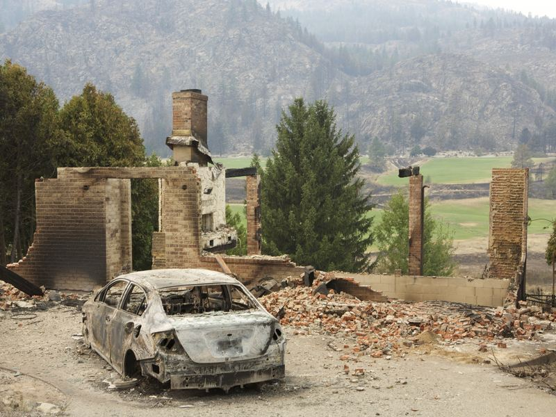 A burned-out car sits in front of a ruined house in this photo taken Sunday near Pateros, Wash. Large fires have destroyed hundreds of homes in the state this month.