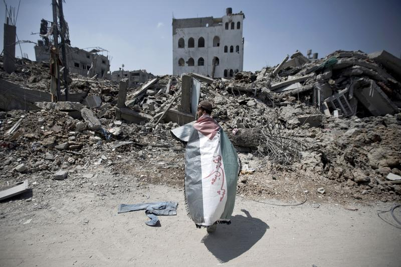 A Palestinian man, wrapped in his national flag, inspects the rubble of destroyed buildings and houses in the Shejaiya residential district of Gaza City, on July 28, 2014, on the beginning of the Muslim Eid festival ending the month-long fast of Ramadan. (Mahmud Hams/AFP/Getty Images)