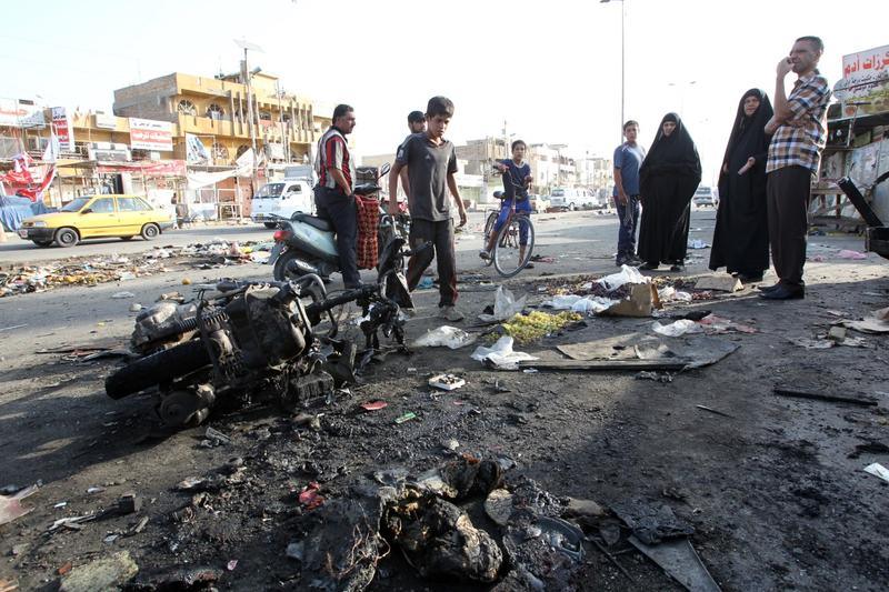 Iraqi onlookers gather on July 16, 2014 around a burnt motorcycle at the scene of an explosion that took place the previous night in Sadr City, one of Baghdad's northern Shiite-majority districts. (Ali al-Saadi/AFP/Getty Images)