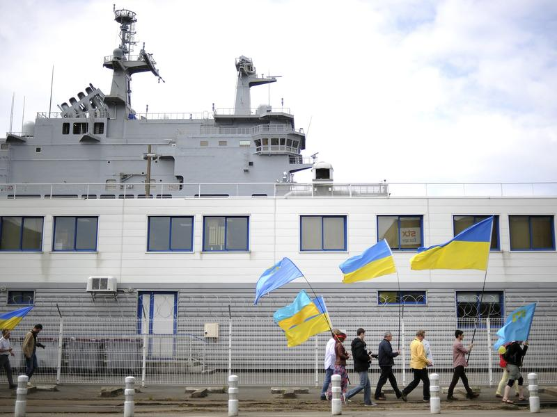 People holding Ukrainian and Crimean Tatar flags demonstrate in front of the French-built Vladivostok warship in St. Nazaire, western France, on June 1. The protesters are opposed to the sale of the Vladivostok and Sevastopol warships to Russia.