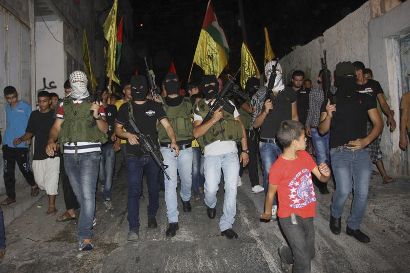 Masked Palestinian militants of Al-Aqsa Martyrs Brigades, march during a demonstration against the Israeli military action in Gaza, in Balata refugee camp in the West Bank city of Nablus, Saturday, July 26, 2014. (Nasser Ishtayeh/AP)