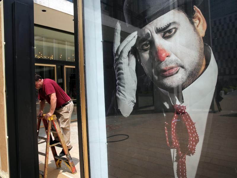 A worker unveils posters Tuesday for the coming season of New York's Metropolitan Opera. The Met's fall schedule could be in jeopardy if failed labor negotiations result in a lockout Friday.