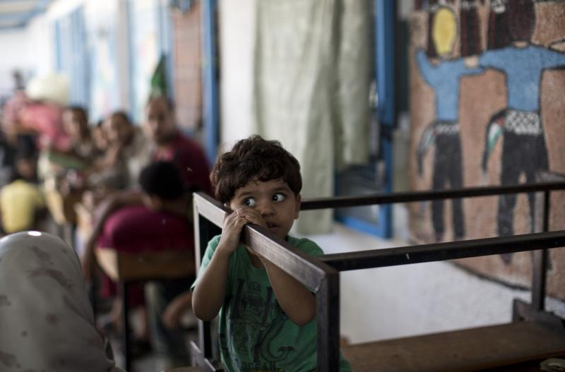 A displaced Palestinian child takes shelter at the Abu Hussien UN school in the Jabalia refugee camp in the northern Gaza Strip after the area was hit earlier in the morning by Israeli shelling on July 30, 2014. Israeli bombardments early on July 30 killed dozens of Palestinians in Gaza, including those at at a UN school, medics said, on day 23 of the Israel-Hamas conflict. (Mahmud Hams/AFP/Getty Images)