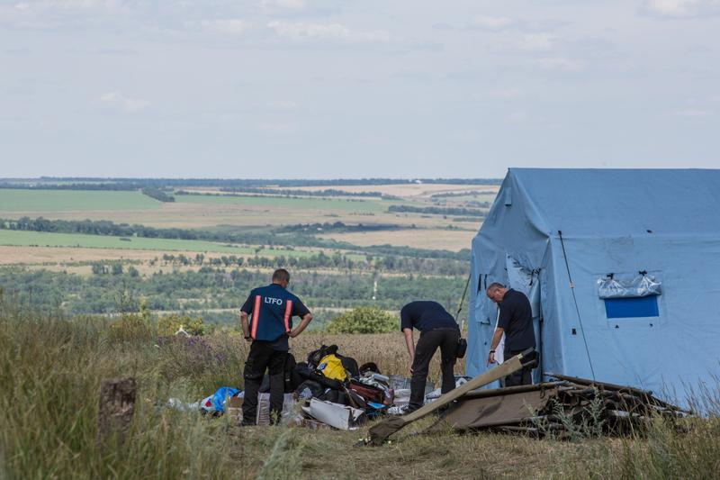 Inspectors from the Dutch government examine items at the Malaysia Airlines flight MH17 crash site on July 21, 2014 in Grabovo, Ukraine. (Brendan Hoffman/Getty Images)
