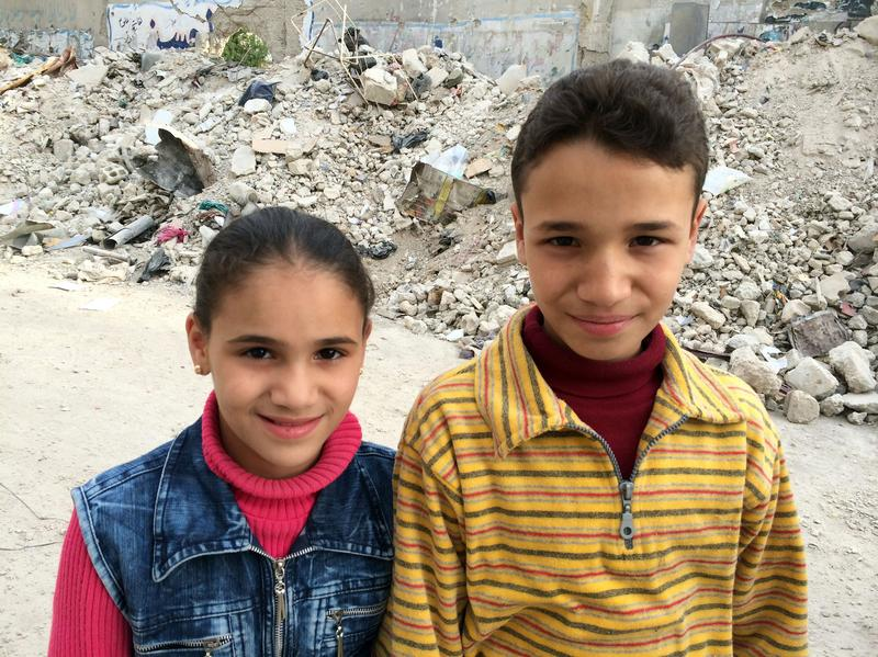 Kifah, 13, poses with his sister in Damascus. Kifah is one of six Syrian children profiled in a new BBC documentary.