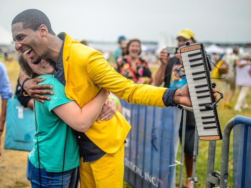 Jon Batiste embraces the crowd at the 2014 Newport Jazz Festival.