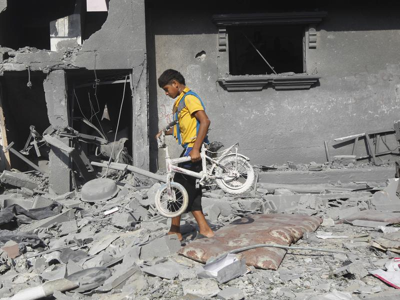 A Palestinian youth carries a bicycle from the wreckage of a building hit in an Israeli strike in Rafah in the southern Gaza Strip Saturday. New violence killed dozens in Gaza after the collapse of a UN- and U.S.- backed cease-fire, officials said.