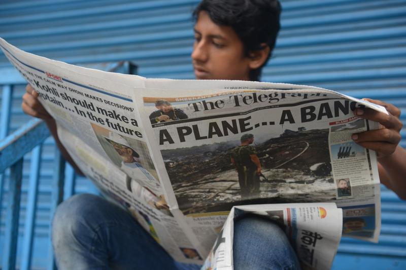 An Indian man reads a newspaper with the news featuring the crash of a Malaysia Airlines plane carrying 298 people from Amsterdam to Kuala Lumpur at a newspaper stand in Siliguri on July 18,2014. (Diptendu Dutta/AFP/Getty Images)