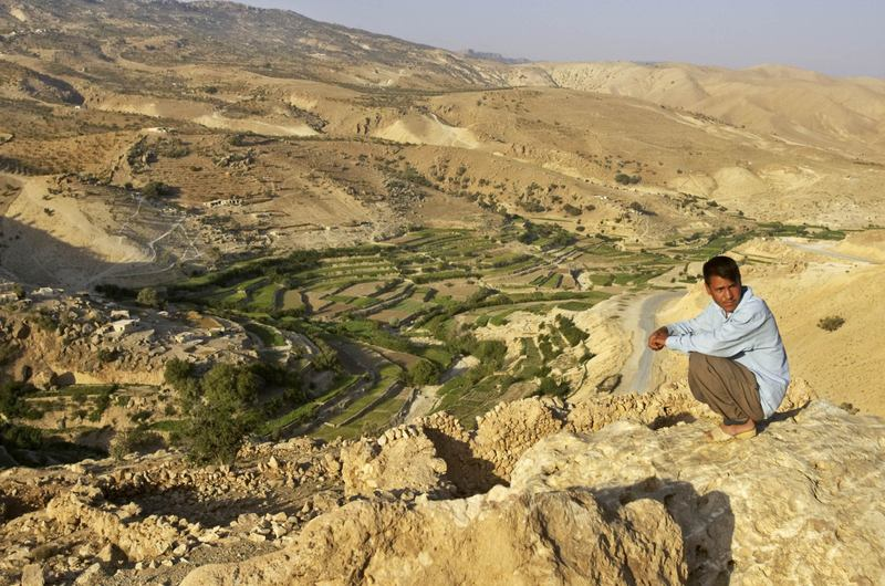 A Yazidi man sits on a cliff above the terraces his village uses for farming on Mount Sinjar in Iraq, Sept. 19, 2005. Today, tens of thousands of Yazidis are trapped on the mountaintop. (Jacob Silberberg/AP)