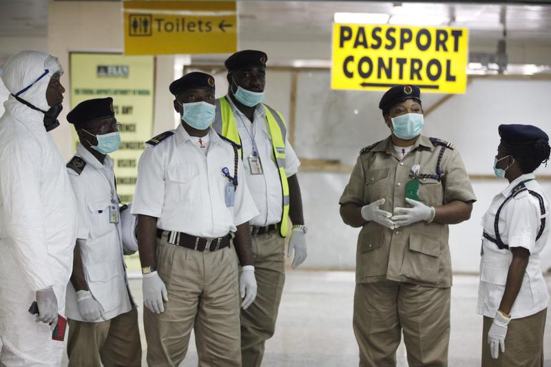Nigeria health officials wait to screen passengers at the arrival hall of Murtala Muhammed International Airport in Lagos, Nigeria, Monday, Aug. 4, 2014. (Sunday Alamba/AP)