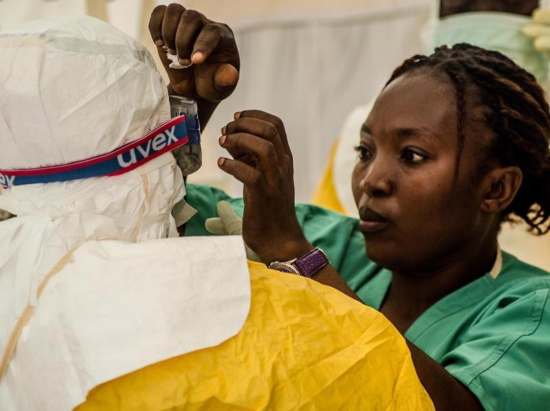 A nurse helps a health worker put on protective gear before treating Ebola patients at a clinic in Kailahun, Sierra Leone, in July.