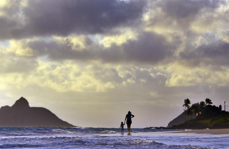 Anne Kllingshirn, of Kailua, Hawaii walks with her daughter Emma, 1, as storm clouds float overhead during the sunrise hours on Kailua Beach, in Kailua, Hawaii, Thursday morning Aug. 7, 2014. (Luci Pemoni/AP)