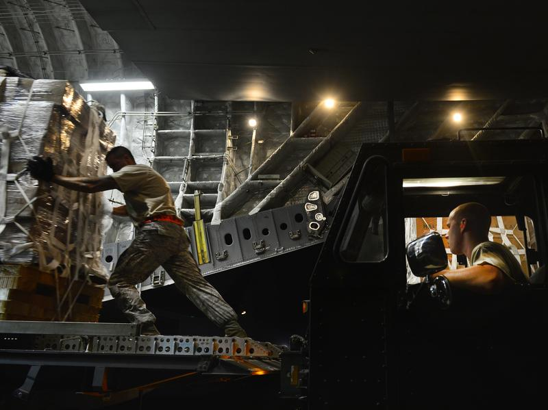 Staff Sgt. Daniel Leavindofske and Senior Airman David Babcock help load bundles of halal meals onto a cargo aircraft for a humanitarian mission over Iraq on Saturday.