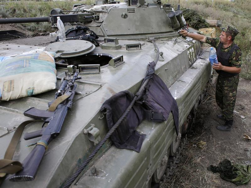 A Ukrainian soldier cleans his armored personnel carrier near Donetsk in eastern Ukraine Monday. Russia says a large convoy that's heading to the area from Moscow is carrying humanitarian aid.