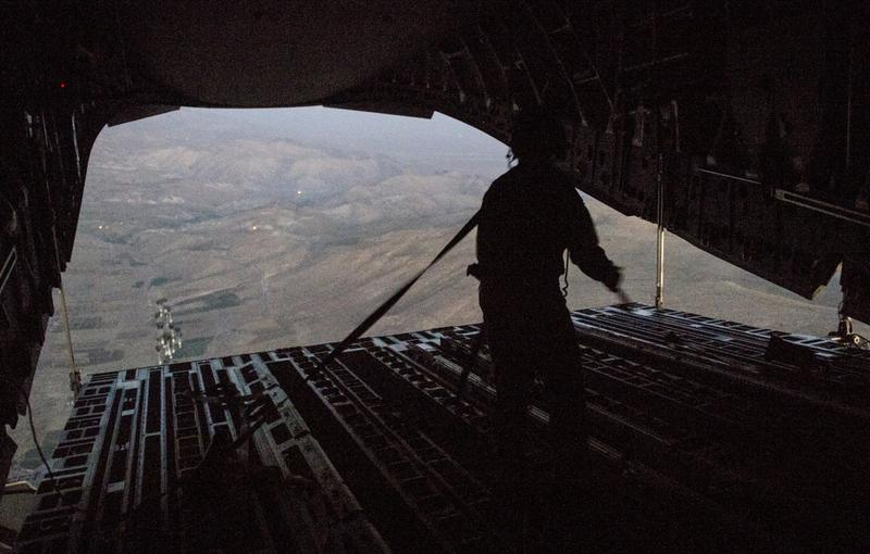 In this image provided by the U.S. Department of Defense, Tech. Sgt. Lynn Morelly, 816th Expeditionary Airlift Squadron, C-17 Globemaster III loadmaster, watches bundles of halal meals parachute to the ground during a humanitarian airdrop mission on August 9, 2014 over Iraq. (Staff Sgt. Vernon Young Jr./U.S. Air Force via Getty Images)