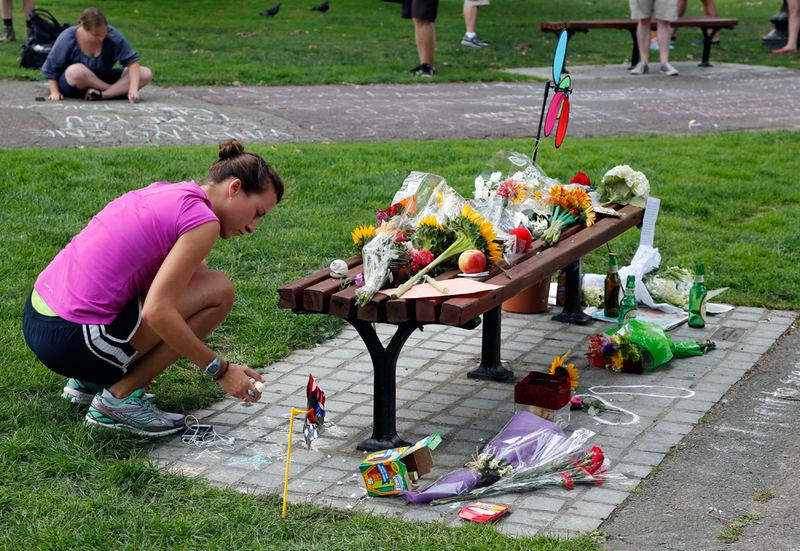 "People write chalk messages by a bench at Boston's Public Garden Tuesday, where a small memorial has sprung up at the place where Robin Williams filmed a scene during the film ""Good Will Hunting."" (Elise Amendola/AP)"