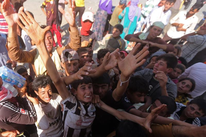 Displaced Iraqi Yazidis, who fled a jihadist onslaught on Sinjar, gather to collect bottles of water at the Bajid Kandala camp in Kurdistan's western Dohuk province, on August 13, 2014. Scores of young men and children held a protest demanding more aid at the Bajid Kandala camp that is hosting thousands of desperate Iraqi Yazidis. (Ahmad Al-Rubaye/AFP/Getty Images)
