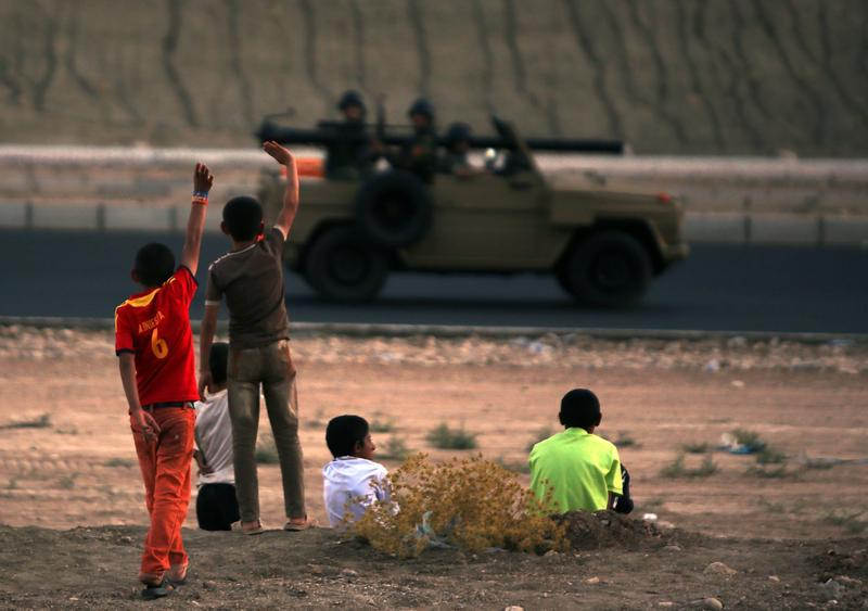 Iraqi children from the Yazidi community wave to Kurdish Peshmerga forces near Dohuk, the Kurdish region of autonomous Kurdistan in Iraq, after they fled with their families their hometown which was attacked by Sunni militants from the Islamic State, on August 12, 2014. (Ahmad al-Rubaye/AFP/Getty Images)