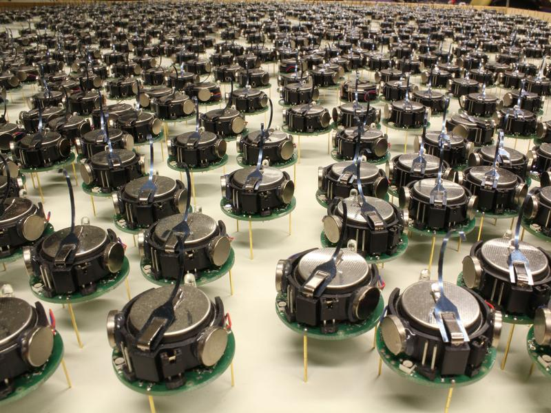 "These 1024 ""kilobots"" can shuffle into any shape their creator desires. Each robot is a little bigger than a quarter, standing on three little metal legs that vibrate to make it move."