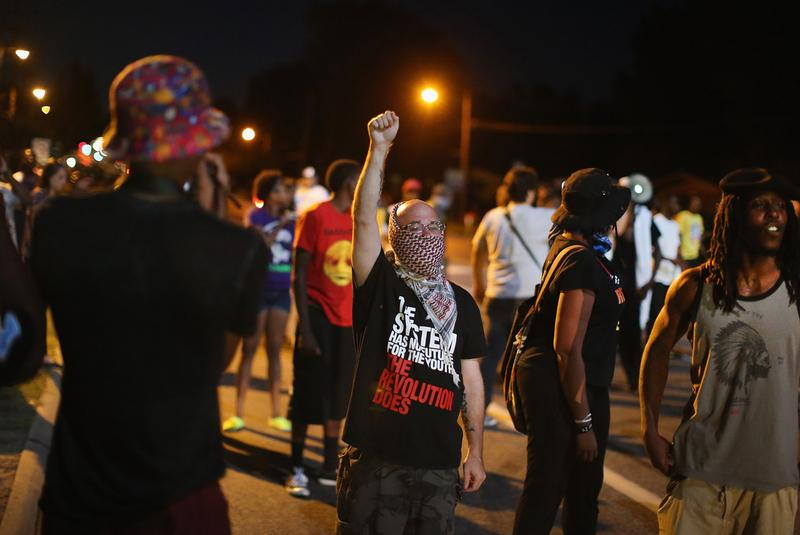 Demonstrators protest the shooting death of teenager Michael Brown on August 13 in Ferguson, Missouri. Brown was shot and killed by a Ferguson police officer on Saturday. Ferguson, a St. Louis suburb, is experiencing its fourth day of violent protests since the killing.  (Scott Olson/Getty Images)